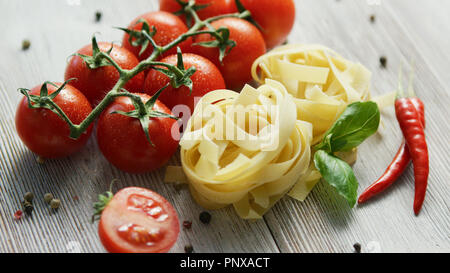 Uncooked pasta bunches with tomatoes - Stock Photo