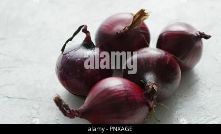 Red onion bulbs on white table - Stock Photo