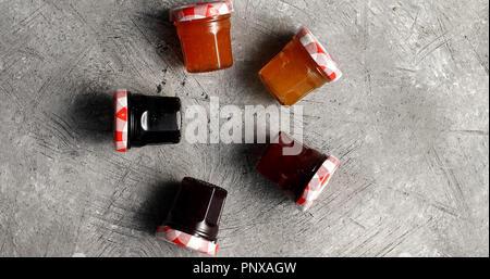 Small jars with various marmalade - Stock Photo