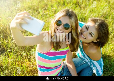 Portrait of beautiful adult mother and her daughter teenage girl making a selfie using a smart phone and smiling.  Photo taken in nature, summer day - Stock Photo