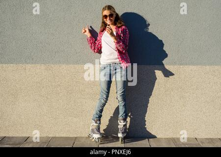 Portrait of young cool girl, shod in rollerblades holding chocolate bar and showing thumbs up. Thumb up energy and joy - Stock Photo