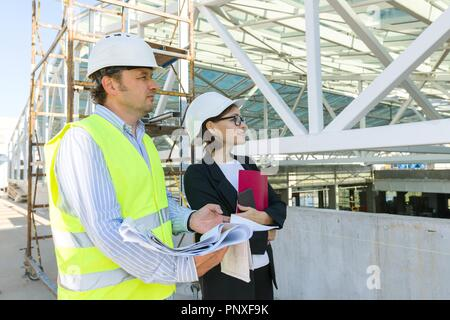 Man engineer and woman architect at a construction site. Building, development, teamwork and people concept. - Stock Photo