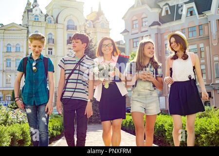 Teacher's Day, outdoor portrait of happy middle aged female high school teacher with bouquet of flowers and group students - Stock Photo