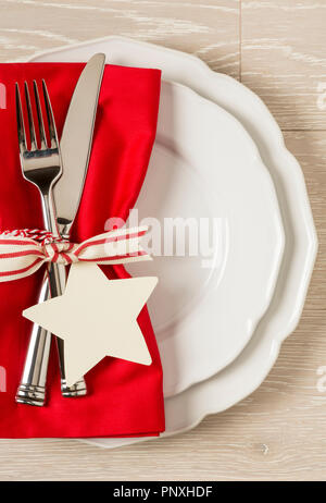 Festive Christmas table setting place setting with white china plates, red cloth napkin and silverware on rustic wood background. Vertical with empty  - Stock Photo