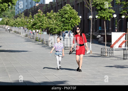 Tashkent, Uzbekistan - May 01, 2017: Playful mother and daughter walks happily in the pedestrian sideways. - Stock Photo