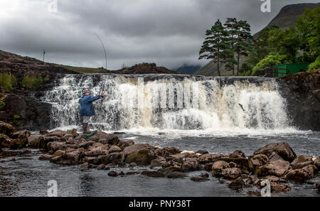 Ashleigh Falls, Mayo, Ireland. 06th August 2006. A angler on a fishing holiday casts his line while a Salmon attempts to  leap the falls on its way up - Stock Photo