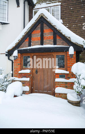 Wooden oak front door and porch of a large house with undisturbed drifting snow during heavy snowfall in winter, Woking, Surrey, southeast England, UK - Stock Photo