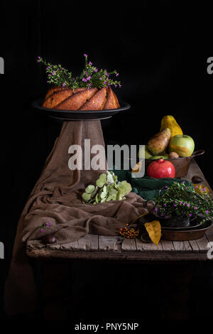 Autumn still life with bundt cake and seasonal fruit on old wooden table. - Stock Photo