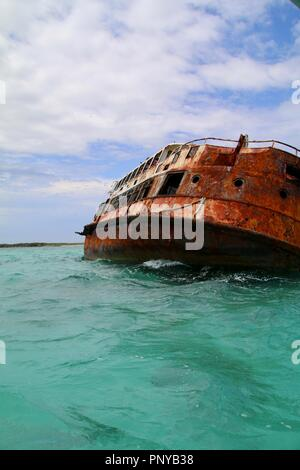 A rusty wreck laying on it 's side in the Caribbean, wrecked by a hurricane - Stock Photo