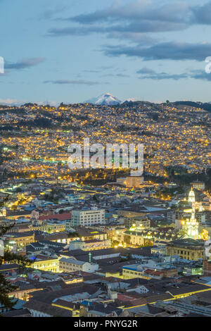 View of Quito at night and Cotopaxi volcano in the background, Ecuador - Stock Photo
