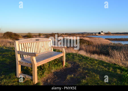 A seat facing west as the sun sets on Cliffe marshes in Kent, England, on a winter's day. Late December 2017