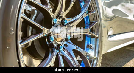 White car with silver tire rim and blue bolts - Stock Photo