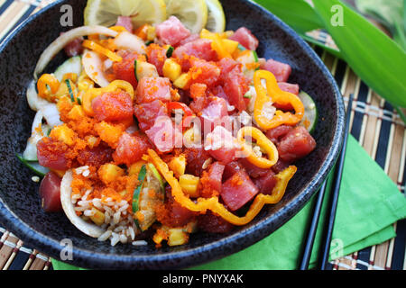 Hawaiian ahi tuna poke bowl served with white rice, vegetables and marinated tuna, close up - Stock Photo