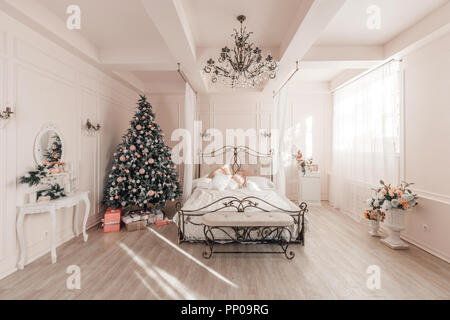 classical interior of a light room. Morning in bedroom. classic apartments with a white fireplace, decorated christmas tree. - Stock Photo