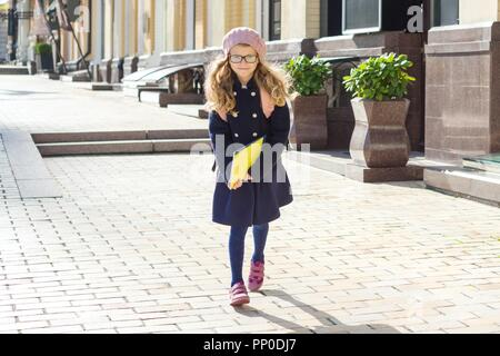 Portrait of little adorable schoolgirl with notebooks and backpack running to school, girl wearing glasses cap, urban style background. - Stock Photo