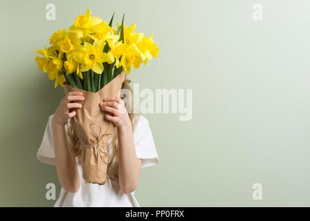 Child girl holding bouquet of yellow narcissus flowers. Gift, surprise, spring family holiday - Stock Photo