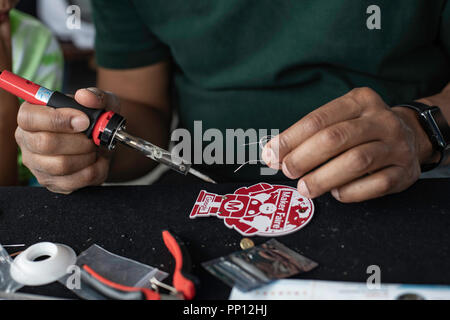 New York, USA, 22nd September, 2018 Jacques Joseitre of Manhattan learns to solder his maker badge at the World Maker Faire in New York City. The festival is a two day event that includes exhibits, workshops and talks on making and the DIY culture.  Credit: L.A. Faille/Alamy Live News - Stock Photo