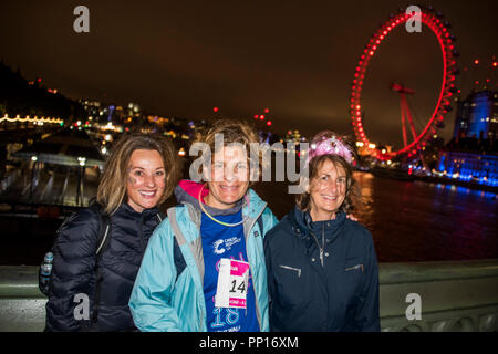 London, UK. 23rd Sep, 2018. Team Warham have raised nearly £90,000 in memory of well known banker Mark Warham who died this year as a result of cancer. Walkers stop on Westminster Bridge to admire the view at midnight. A night walk to raise money for Cancer Research UK. Credit: Guy Bell/Alamy Live News Stock Photo