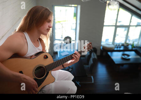 Young man with long hair with a guitar - Stock Photo