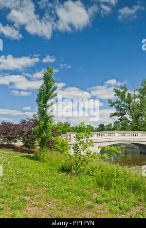 Spectacular sky over the bridge next to purple-leaf redbud trees and a poplar beside the Grand Basin at St. Louis Forest Park. - Stock Photo