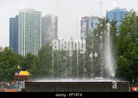 CHICAGO - AUGUST 28: Water droplets dance as the Gateway Park fountain plays in front of fog-enshrouded skyscrapers on a summer afternoon, 2013 Aug. 2 - Stock Photo