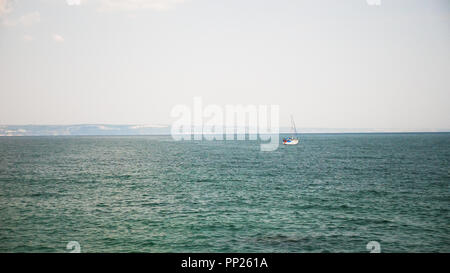 Boat out in of the harbor in deep waters. Sailing skills of humans - Stock Photo