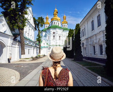 Woman in hat looking at Church with golden domes at Kiev Pechersk Lavra Christian complex. Old historical architecture in Kiev, Ukraine - Stock Photo