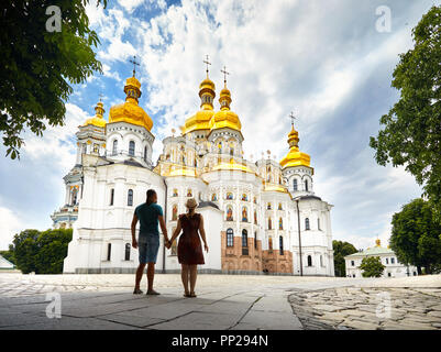 Young tourist couple in silhouette looking at Church with golden domes at Kiev Pechersk Lavra Christian complex. Old historical architecture in Kiev,  - Stock Photo