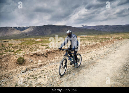 Man on mountain bike rides on the country road in the mountains at stormy sky background.