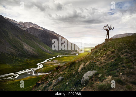 Epic shot of Man holding his mountain bike on the hill in silhouette with the river in the mountain valley background. - Stock Photo