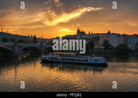 Prague, Czechia - September 19, 2018 : Cruise boat with tourists on Vltava river floats towards the Manesuv bridge with views of Prague Castle at suns - Stock Photo