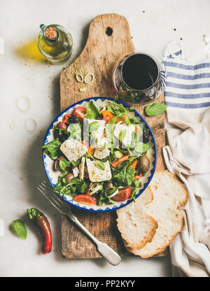 Greek salad with feta cheese, olive oil and red wine - Stock Photo