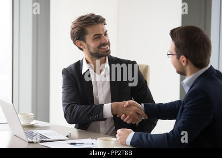 Happy business partners handshaking after successful meeting - Stock Photo