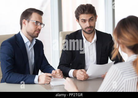 Suspicious recruiters doubting female candidate at interview - Stock Photo