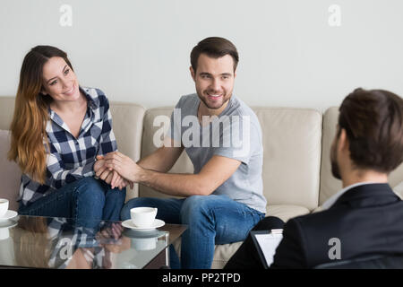 Happy couple holding hands reconciled after psychologist therapy - Stock Photo