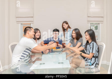 Group of friends drinking and sing song with guitar at home. Concept about friendship, home entertainment and people - Stock Photo