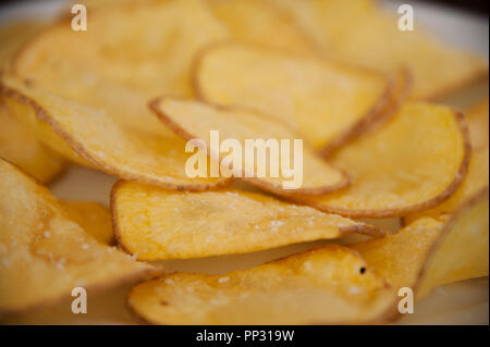 A plate of decorative fried potato chips which are sometimes called crisps - Stock Photo