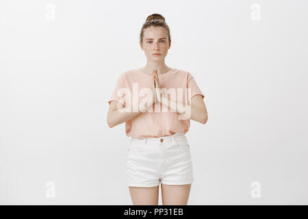 Girl studying martial arts, bowing to sensei. Serious, determined good-looking woman with freckles in trendy summer outfit, holding hands in pray, staring seriously at camera, greeting in asian style - Stock Photo