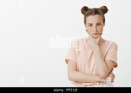 Perplexed smart and determined female student in pink t-shirt with buns hairstyle, holding fingers and jaw and staring at camera, thinking, making choice or decision, standing over gray wall - Stock Photo