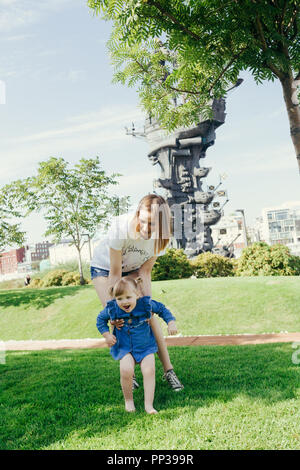 Portrait of a young mother and her 3 years old daughter walking on a lawn in a city park on a warm sunny day - Stock Photo