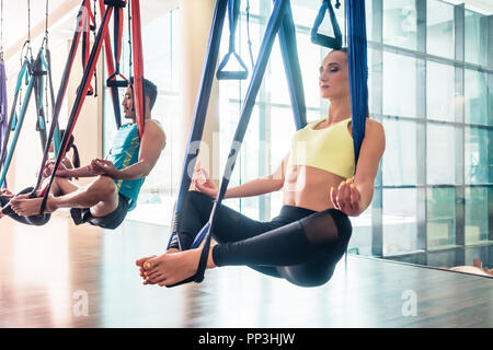 Fit young woman practicing aerial yoga during group class - Stock Photo