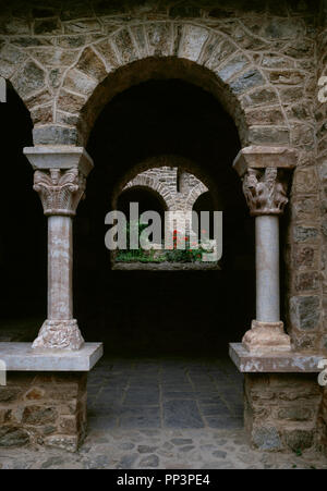 France. Pyrenees-Orientales. Languedoc-Roussillon region. Abbey of Saint-Martin-du-Canigou. Monastery built in 1009, on Canigou mountain. It was built from 1005-1009 by Guifred, Count of Cerdanya in Romanesque style. View of the  semicircular arch of the Cloister. Restoration of 1900-1920. - Stock Photo