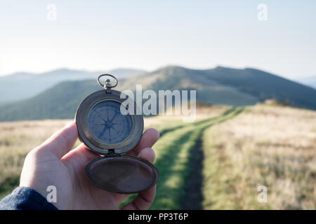 Man with compass in hand on mountains road. Travel concept. Landscape photography - Stock Photo