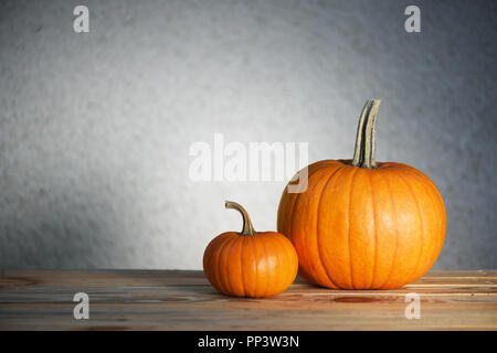 Two pumpkins on wooden table. Halloween and autumn food background - Stock Photo