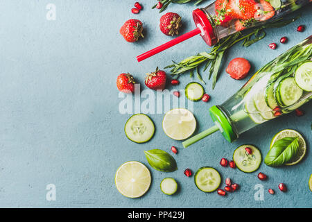 Detox infused water with fruits, berries flavored with fresh herbs and cucumber in bottles with drinking straw, top view - Stock Photo