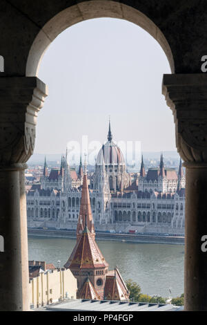 The Hungarian Parliament building seen through the arches of Fishermen's Bastion on Budapest's Castle Hill - Stock Photo