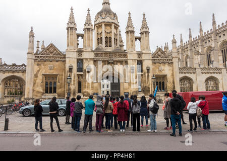 Tourist party in front of Kings college main gate - Stock Photo