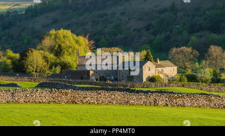 Historic, stone manor house & farm buildings, in beautiful, sunlit countryside nestling under steep hillside - Buckden, Yorkshire Dales, England, UK. - Stock Photo