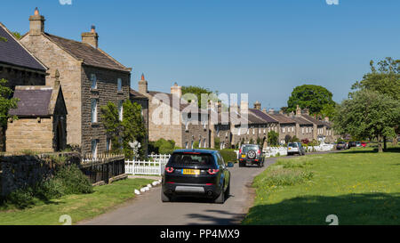 Line of traditional stone cottages facing village green in scenic rural community, 4 Land Rovers passing - East Witton, North Yorkshire, England, UK. - Stock Photo