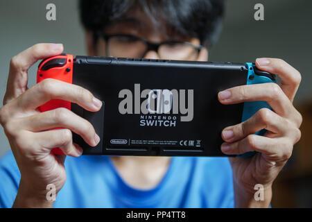 Bangkok, Thailand - July 27, 2018 : A man playing Nintendo Switch. - Stock Photo